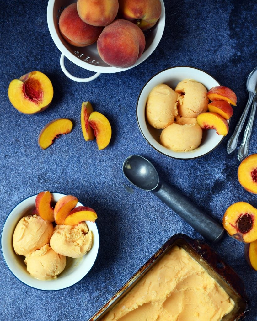 2 bowls of peach sherbet, ice cream scoop, 2 spoons, fresh peach slices, whole peaches, and frozen peach sherbet on a blue background