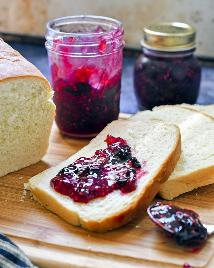 Raspberry blueberry jam spread on a slice of white bread