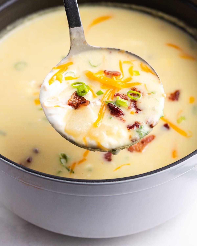 A ladle of baked potato soup above a pot of it.