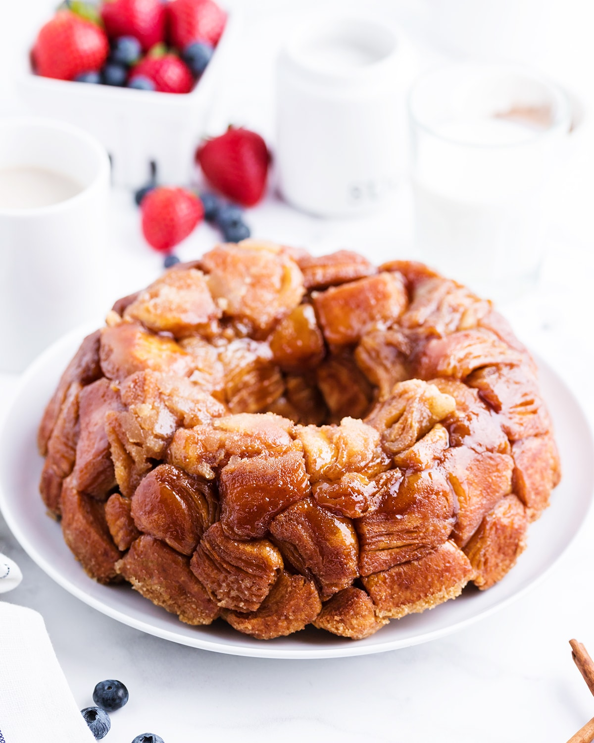 Pull apart monkey bread covered in caramelly sugar goodness, on a white plate.