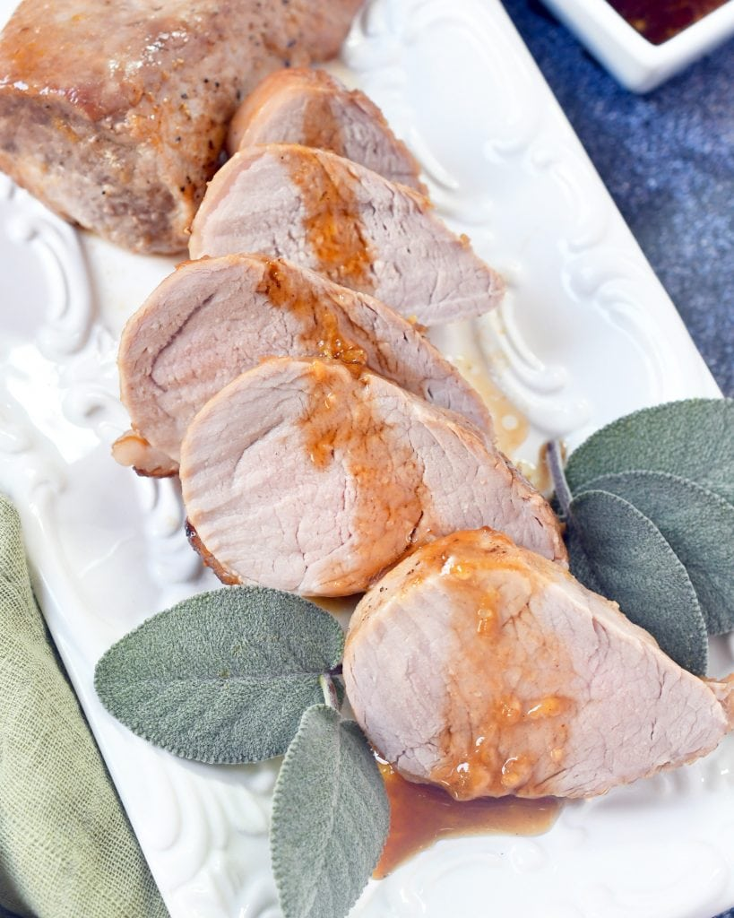 sliced pork tenderloin drizzled with peach honey sauce on a white serving plate framed with sage leaves