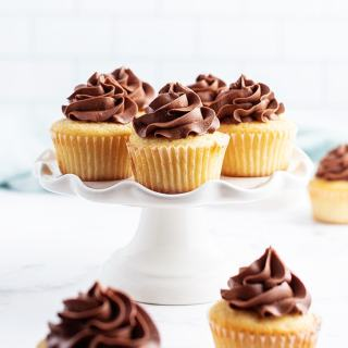Yellow cupcakes on a white cake stand, each swirled with chocolate buttercream frosting on top.