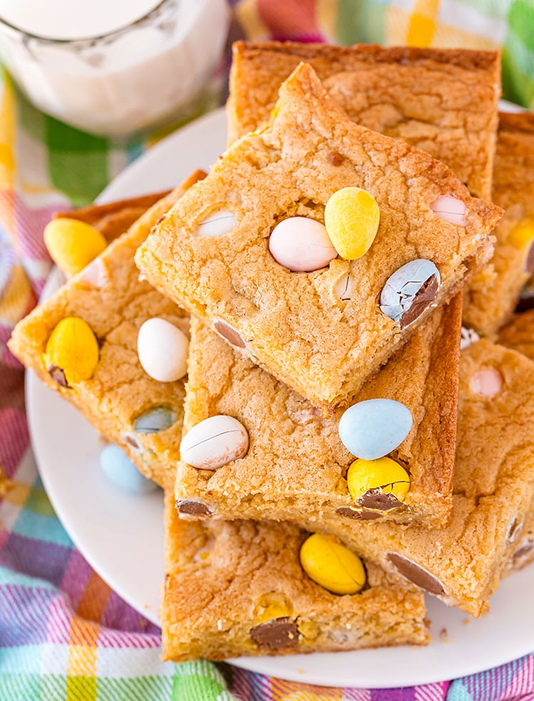 A plate of cookie bars full of cadbury mini eggs stacked in a pile.