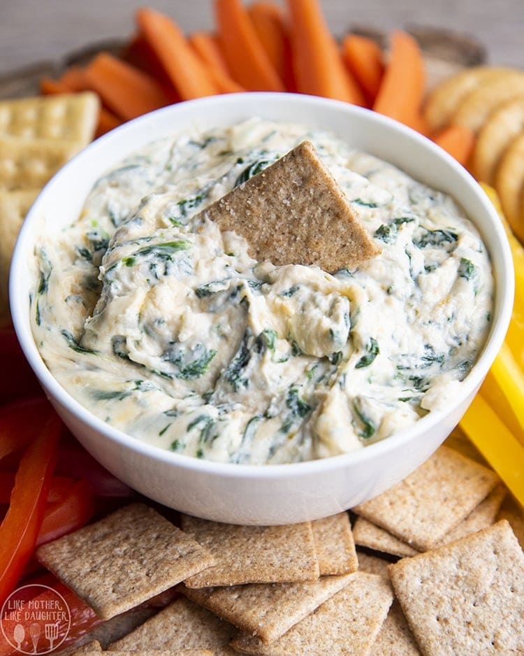 This spinach dip so easy to make at home, in the microwave or oven, and it is the perfect cheesy dip for bread, crackers, or chips!