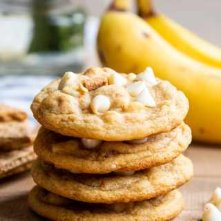 A stack of 4 banana cream pie cookies that are full of and topped with white chocolate chips and graham cracker pieces. There are bananas in the background of the photo.