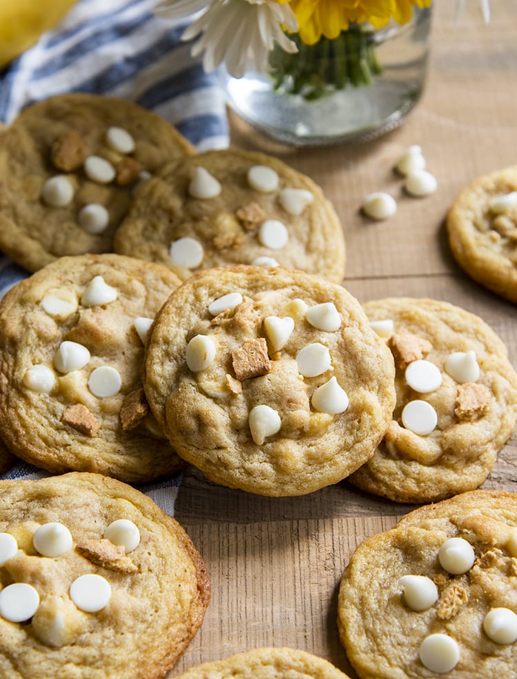A pile of cookies randomly set on each other. The cookies have white chocolate chips and graham crackers on top of them.