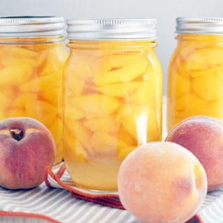 Three jars of bottled peaches with lids on them.