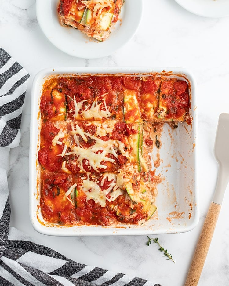 A white square baking dish full of zucchini lasagna shot from above. You can see the red sauce and sprinkles of baked shredded cheese over the top, with a couple pieces cut out of the dish.