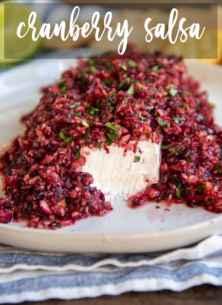 A slab of cream cheese topped with cranberry salsa, full of chopped up cranberries and cilantro. The front of the cream cheese is showing. At the top of the photo there is a text overlay that says Cranberry Salsa.