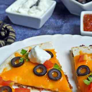 This Mexican Pizza uses 2 layered tortillas stuffed with taco meat, refried beans, cheese, and topped with more cheese, olives, tomatoes, and lettuce.
