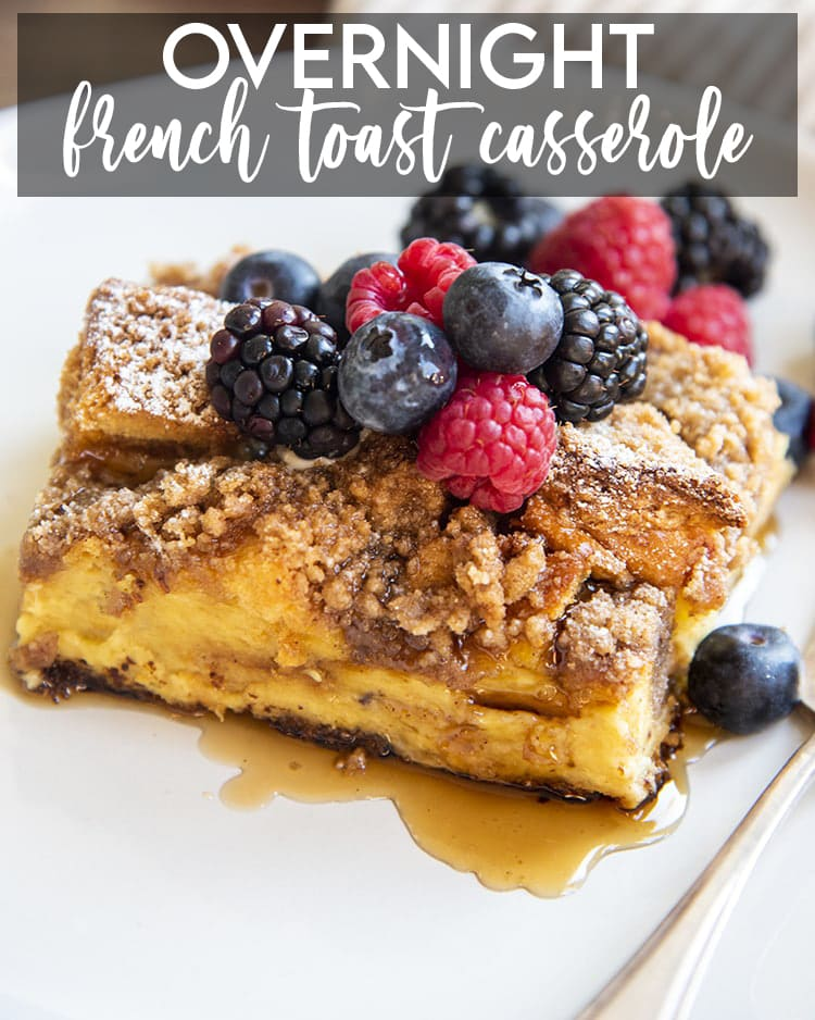 A piece of overnight french toast casserole topped with berries and syrup. There is a text overlay at the top of the photo that says Overnight French Toast Casserole