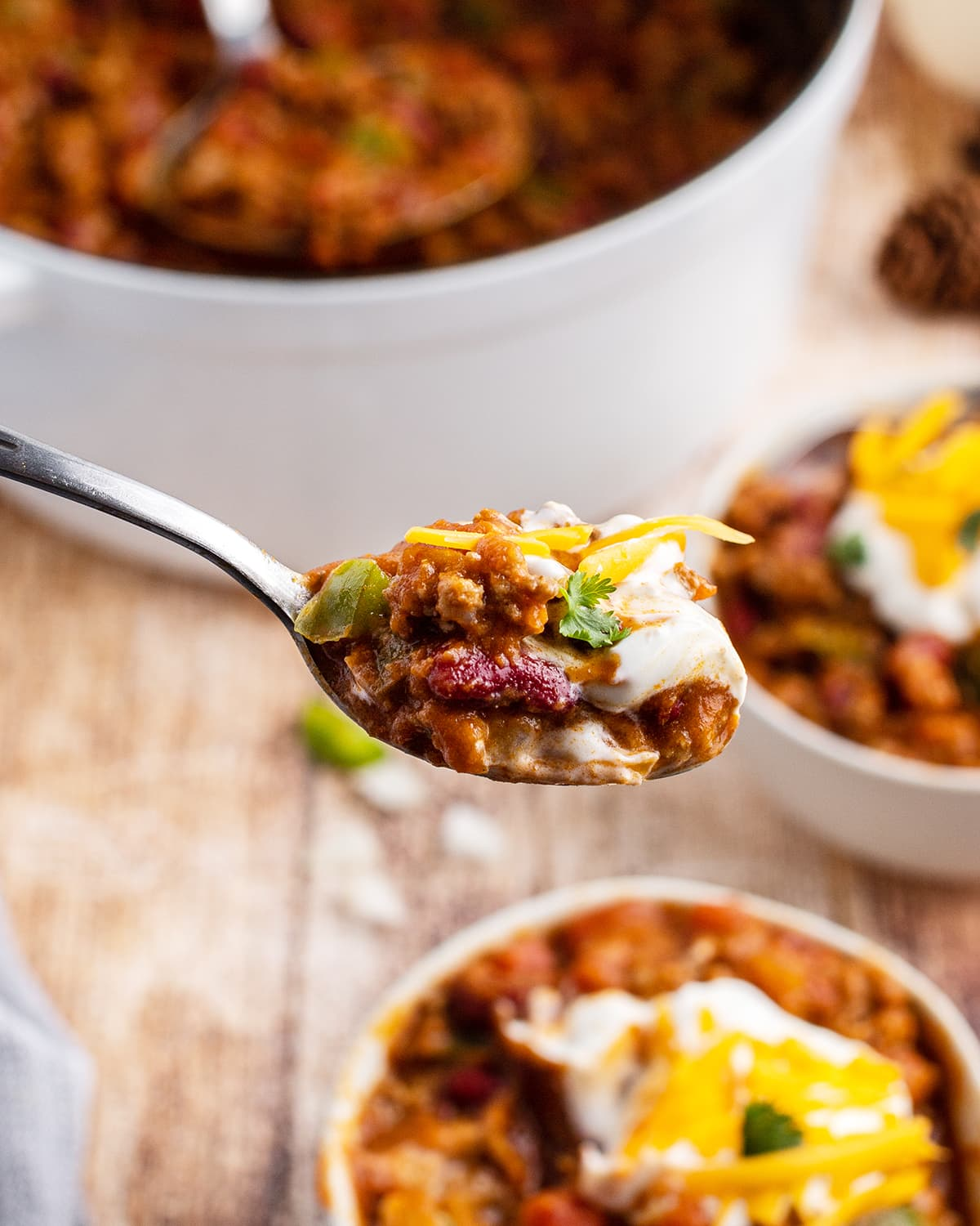 A spoonful of chili topped with cheese and cilantro.