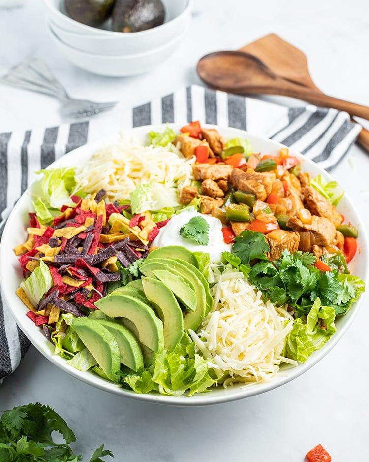 Chicken Fajita salad topped with shredded cheese, avocado, tortilla strips