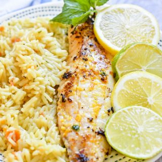 Citrus Butter Tilapia with sliced lemon and limes and rice next to it