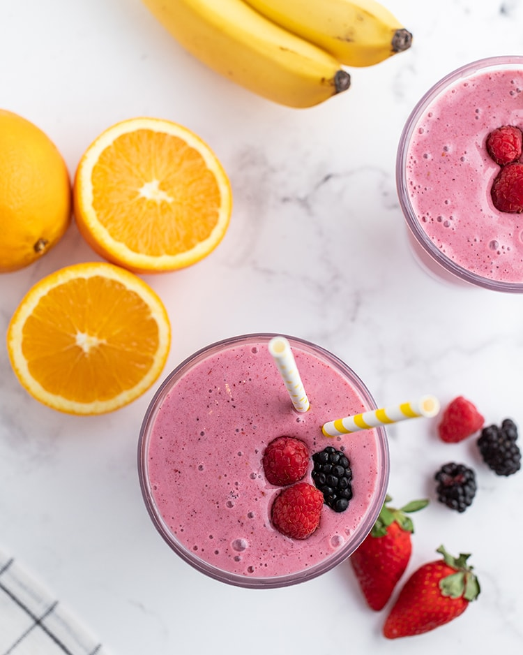 A dark pink smoothie in a glass topped with two raspberries and a blackberry, with two straws, and oranges, bananas, and berries on the side.