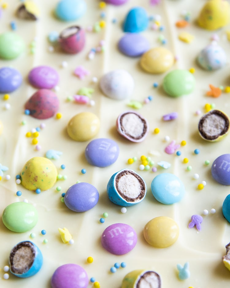A close up of white chocolate Easter bark, sprinkled with pastel colored Easter chocolates and sprinkles.