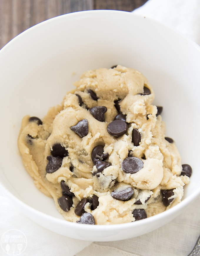 A small bowl full of edible cookie dough with lots of chocolate chips.