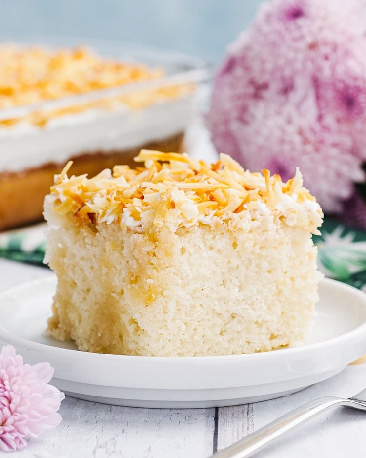A slice of Coconut Cream Poke Cake topped with toasted coconut on a plate.