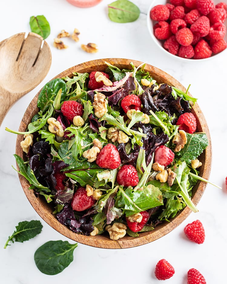 A salad in a wooden bowl with spring mix lettuce, raspberries, and walnuts, with a faint dressing over the salad.