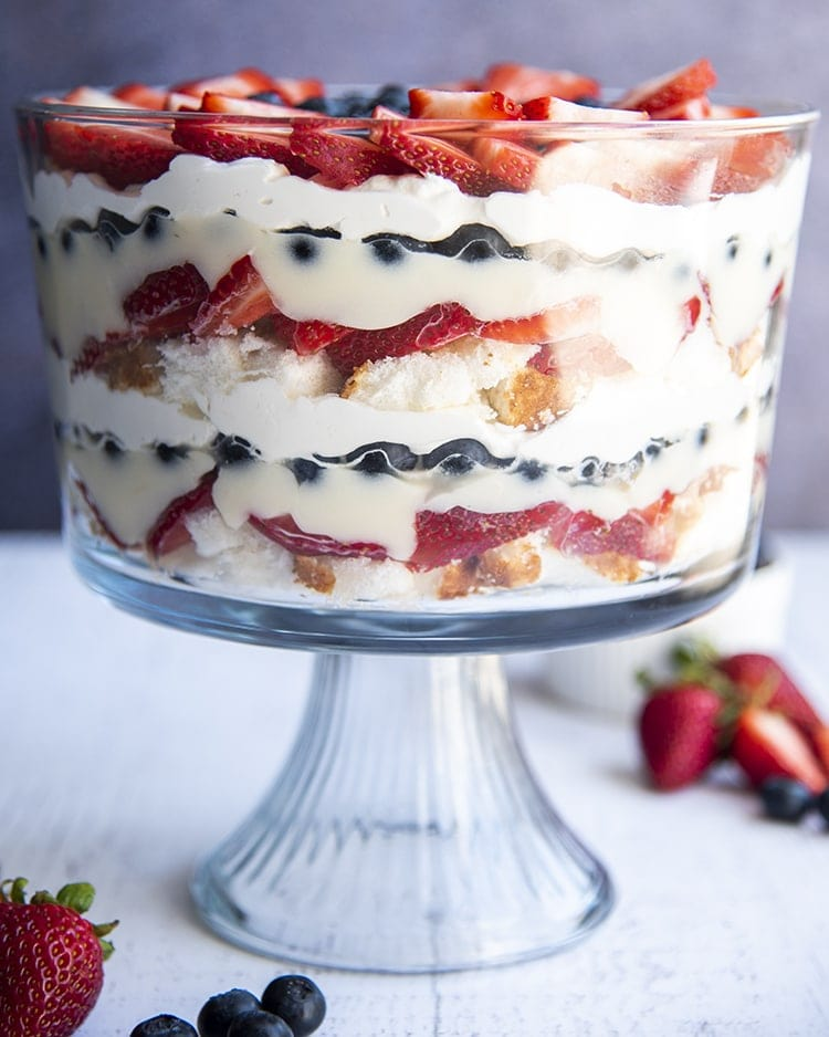 A patriotictrifle with layers of angel food cake, strawberries, pudding, blueberries, and whipped cream