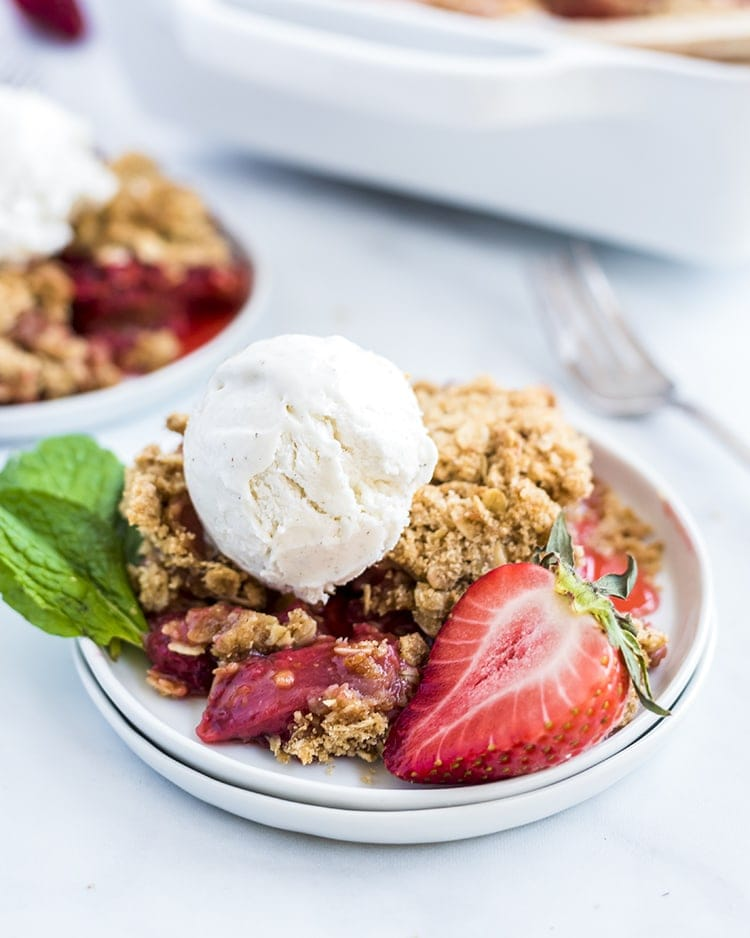 Strawberry Crumble on a white plate with a fresh strawberry and a scoop of vanilla ice cream