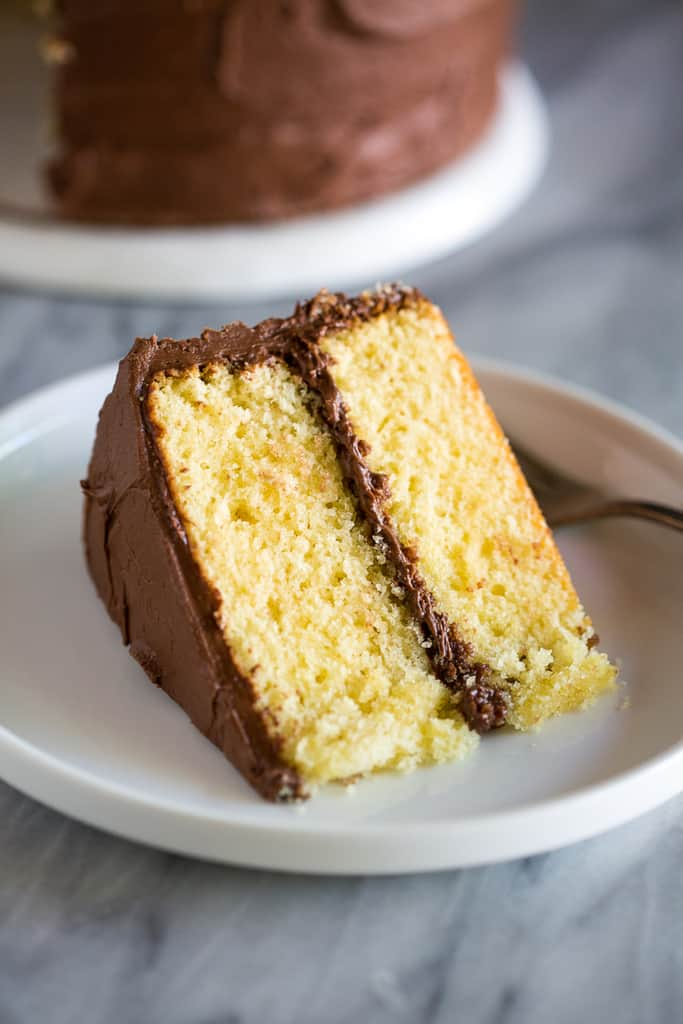 A slice of yellow cake with chocolate frosting
