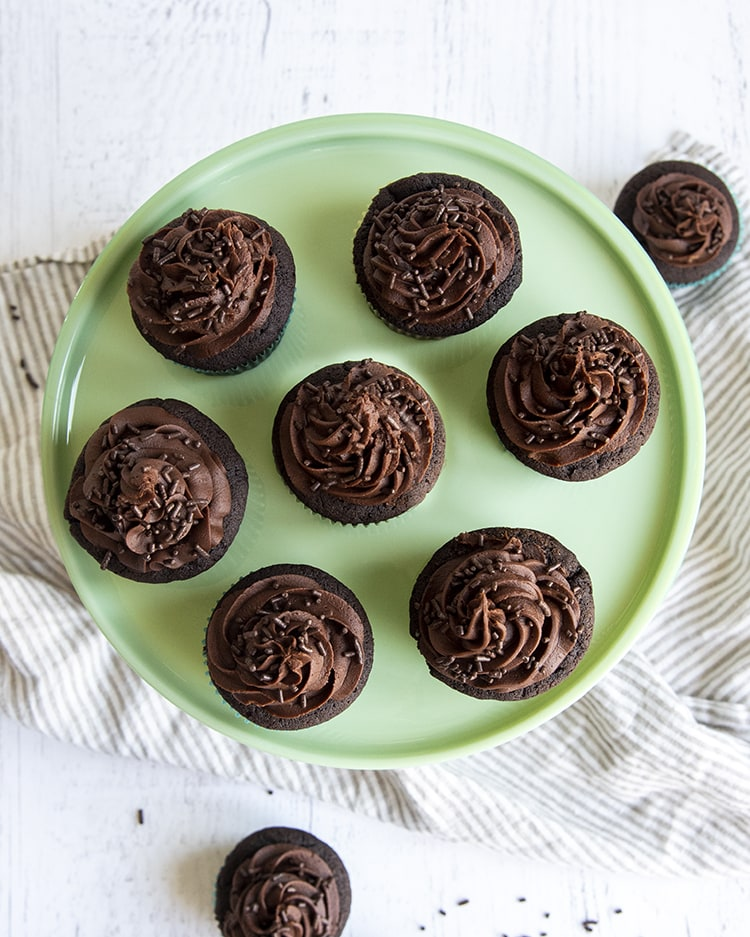 An overhead shot of chocolate cupcakes with chocolate buttercream frosting.
