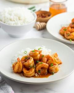 A plate of shrimp with an orange reddish sauce on it, and sprinkled with green onions.