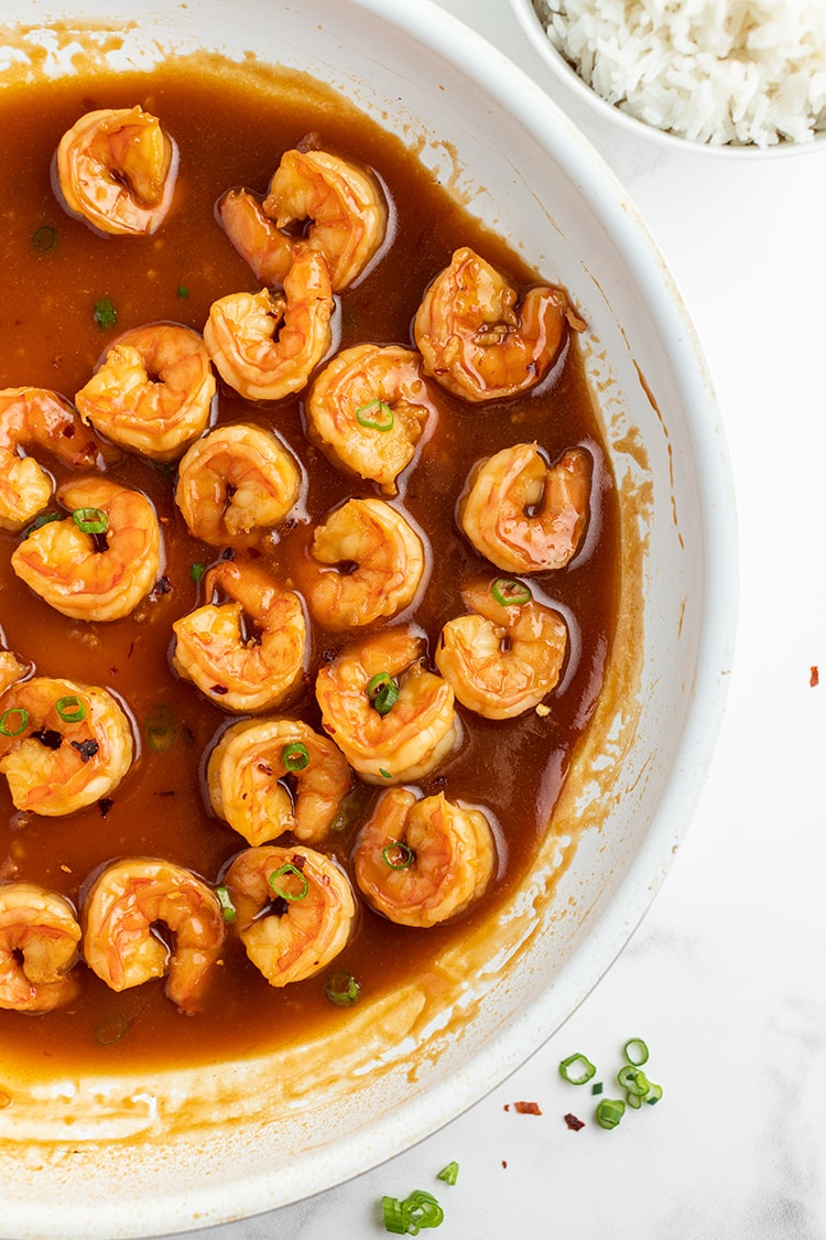 Shrimp cooking in a reddish sauce in a saute pan. Sprinkled with green onions.