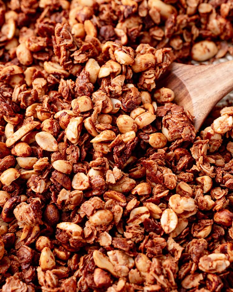 Peanut butter granola spread out with a wooden spoon under some of it.