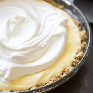 A banana cream pie in a glass pie plate, with a graham cracker crust, yellow pudding filling, and topped with a swirl of whipped cream.