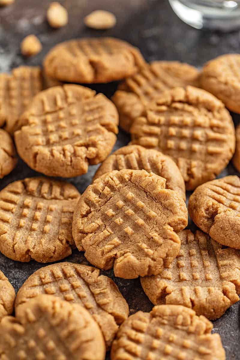A pile of peanut butter cookies. The cookies are pressed on the top with a fork to make a criss cross pattern.