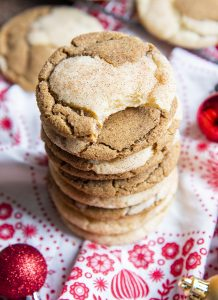 A stack of half ginger molasses, half snickerdoodle cookie swirled together. The top cookie has a bite taken out of it.