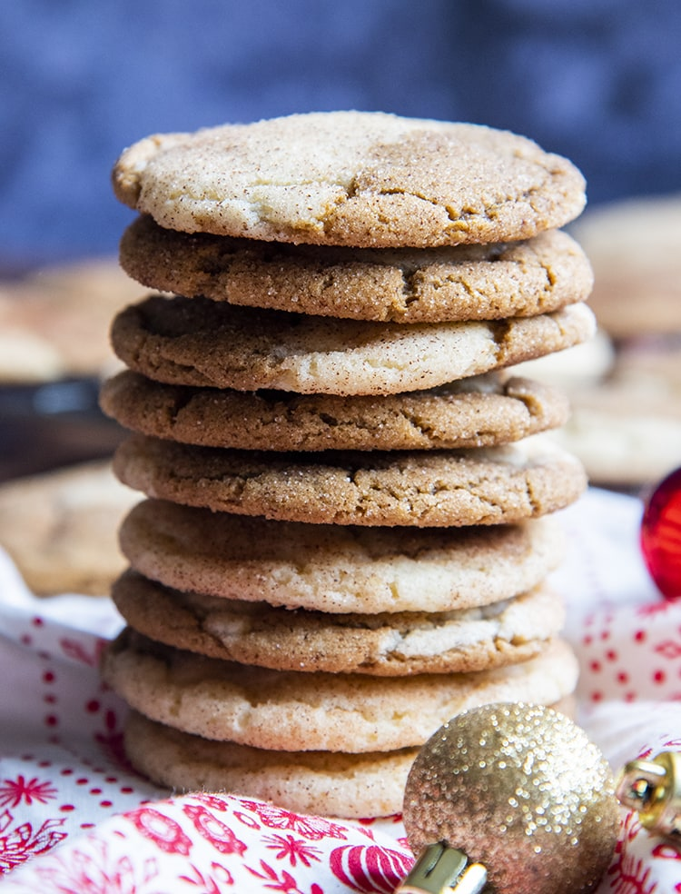 A stack of gingerdoodle cookies, 9 cookies high on a red and white cloth with small Christmas ornaments around.