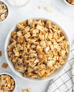 A large bowl of coconut chex mix, that is full of chex, golden grahams, sliced almonds, and shredded coconut.