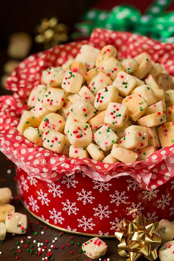 A red Christmas tin full of red tissue paper and funfetti shortbread bites, full of red and green sprinkles.