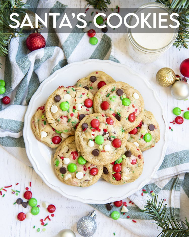 A plate of Christmassy chocolate chip cookies with red and green m&ms, perfect for Santa. There is a text overlay at the top of the photo that says Santa's Cookies.