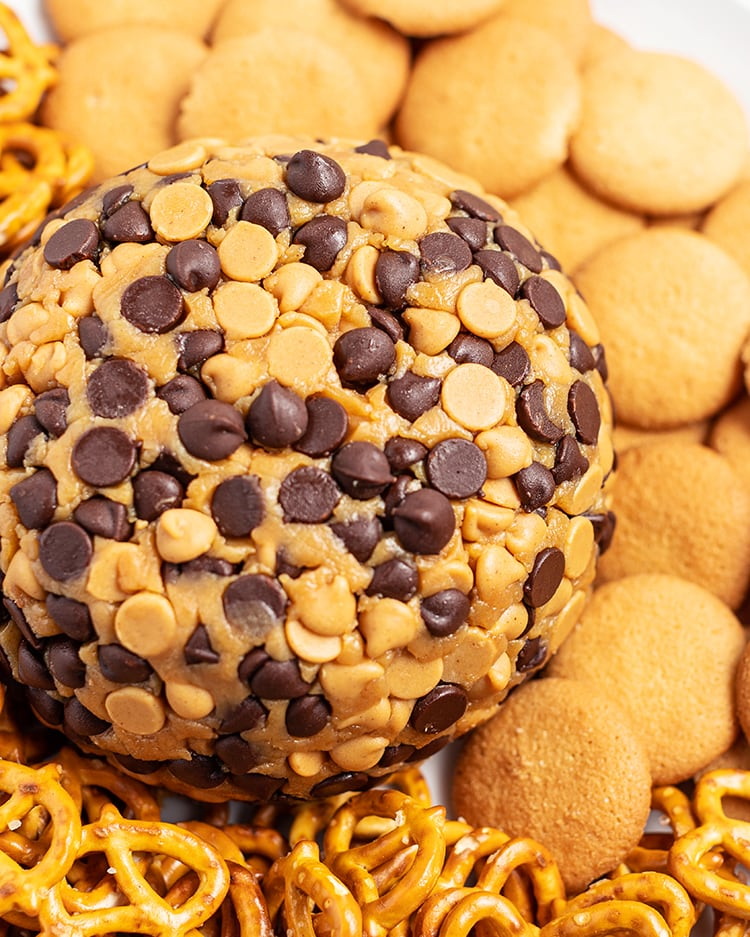 A close up shot of a peanut butter ball coated in peanut butter chips and chocolate chips, surrounded by nilla wafers.
