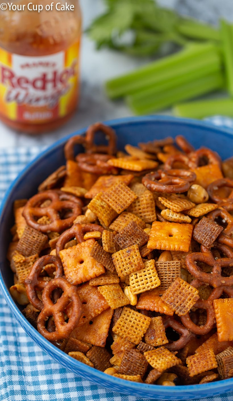 A bowl of buffalo chex mix, it is darker in color with cheese nips, pretzels, and mixed nuts.