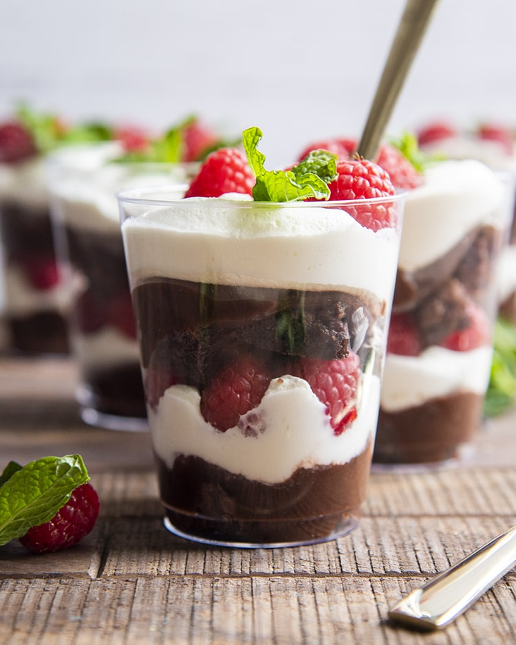 A side shot showing all the layers of a brownie trifle cup. The bottom shows chocolate pudding, then whipped cream, raspberries, brownies, pudding, whipped cream, raspberries, and a mint sprig on top. The cup has a gold spoon in it.