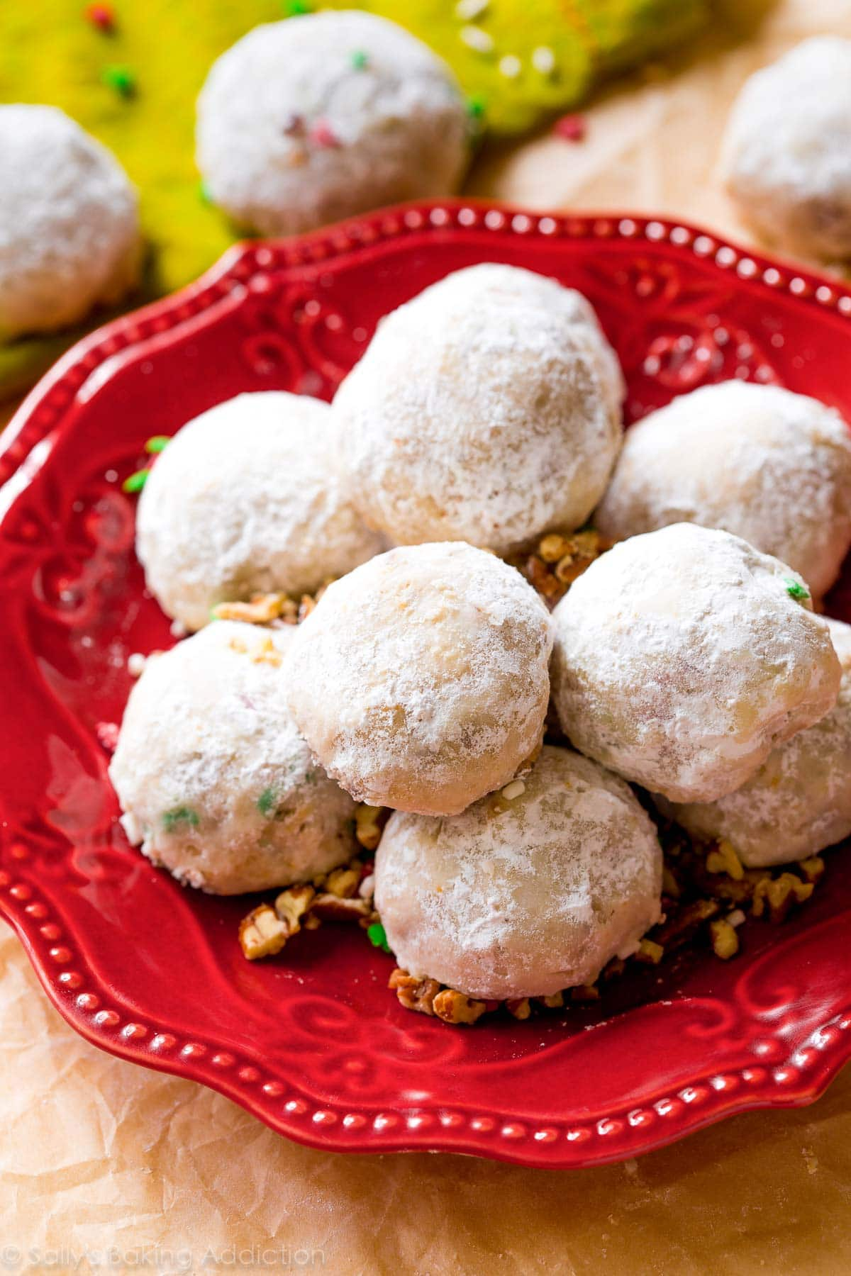 A pile of pecan snowball cookies on a red plate.