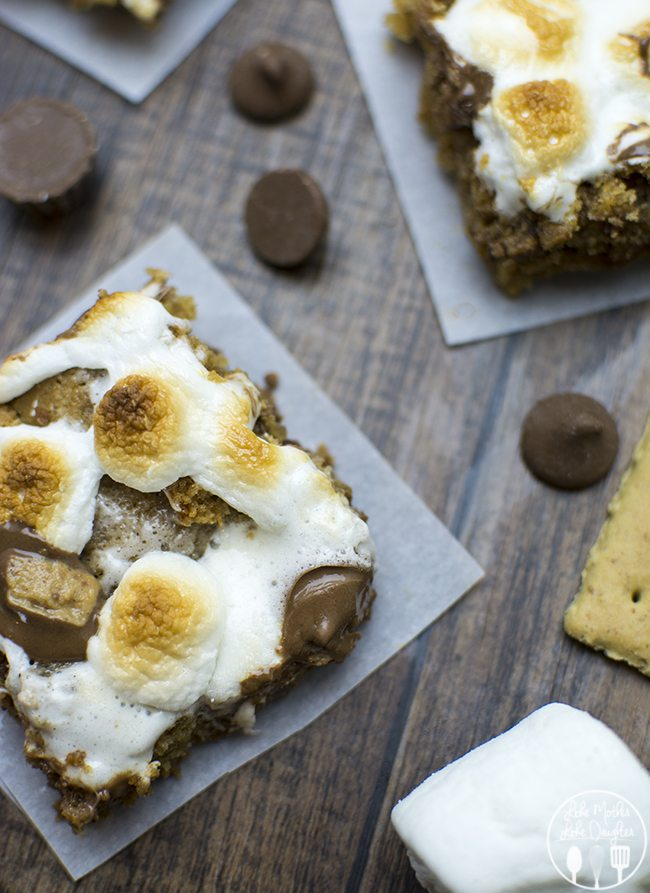 S'mores Peanut Butter Cookie Bars - These delicious peanut butter cookie bars are filled with reeses peanut butter cups and chocolate chips and topped with marshmallows are the perfect combo of s'mores and peanut butter for a seriously delicious treat!