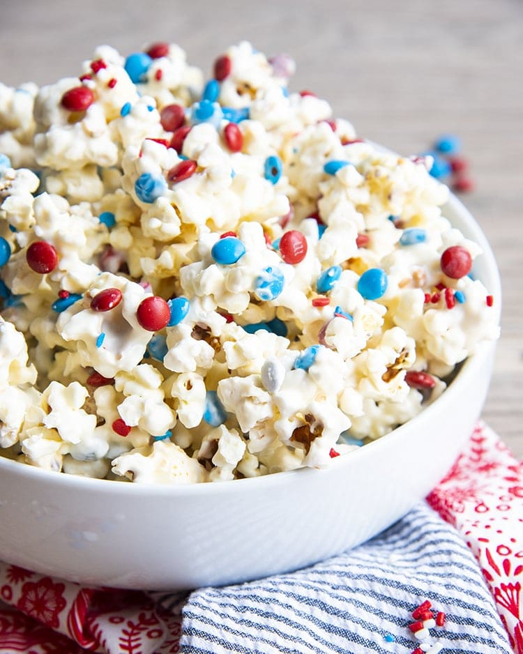 White Chocolate covered Popcorn with red white and blue m&ms and sprinkles in a white bowl