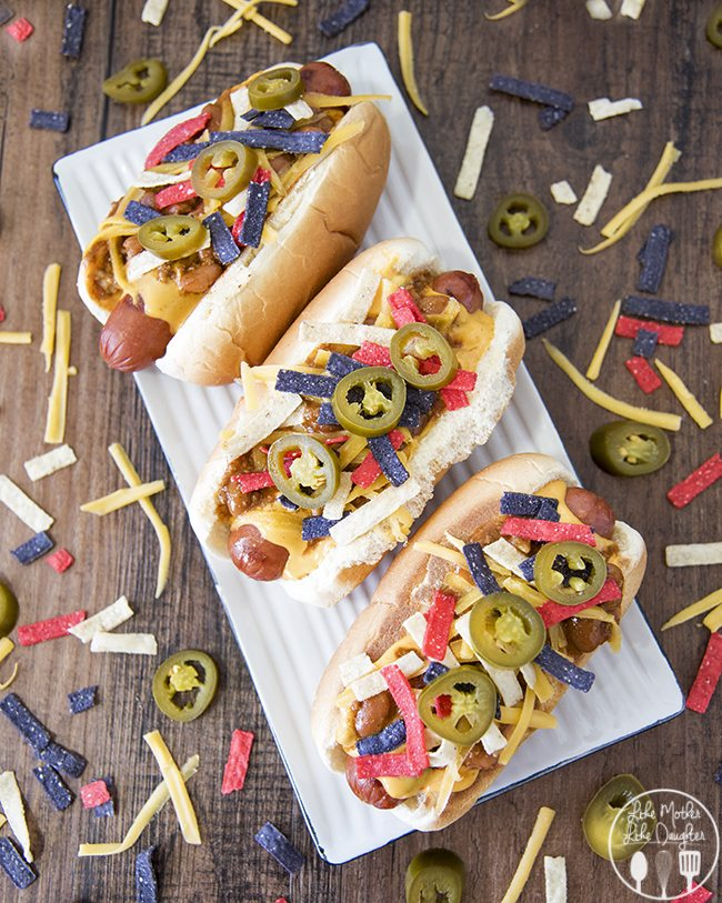 Nacho Dog - this delicious all american hot dog is topped with nacho cheese, chili, shredded cheese, tortilla strips and jalapenos for a delicious summer dish!