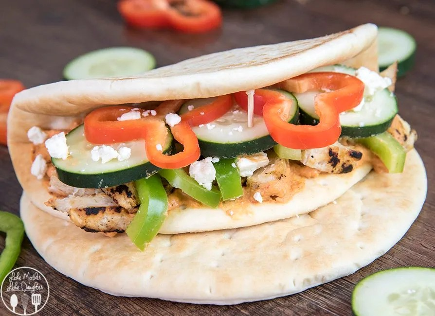 Chicken and Red Pepper Hummus Flatbread- This flatbread sandwich is spread with roasted red pepper hummus, and stuffed full of grilled chicken, sliced cucumbers, red peppers and green peppers and topped with feta cheese for a delicious and healthy sandwich perfect for lunch or dinner!