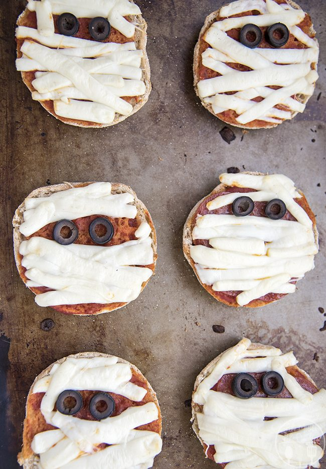 Mummy Mini Pizzas - Delicious and easy mummy pizzas start with an English muffin base, string cheese bandages and olives for eyes and make the perfect Halloween meal!