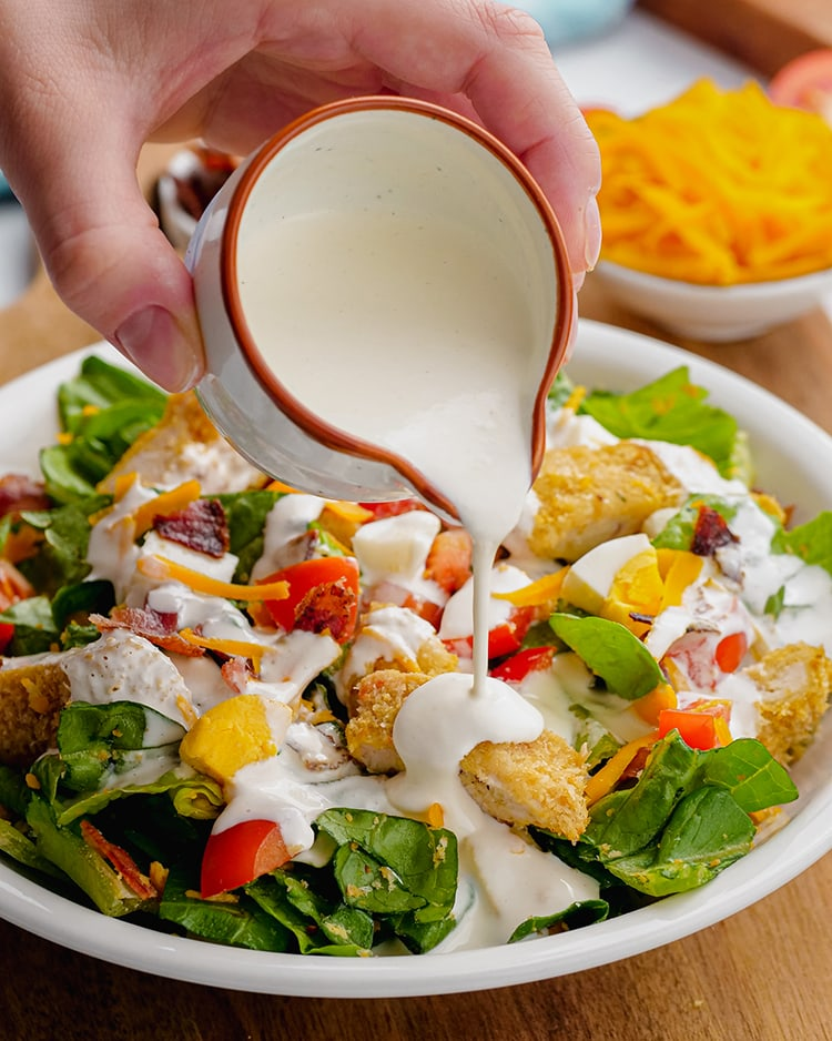 Ranch dressing being poured out of a small cup onto a salad with crispy chicken and diced tomatoes.