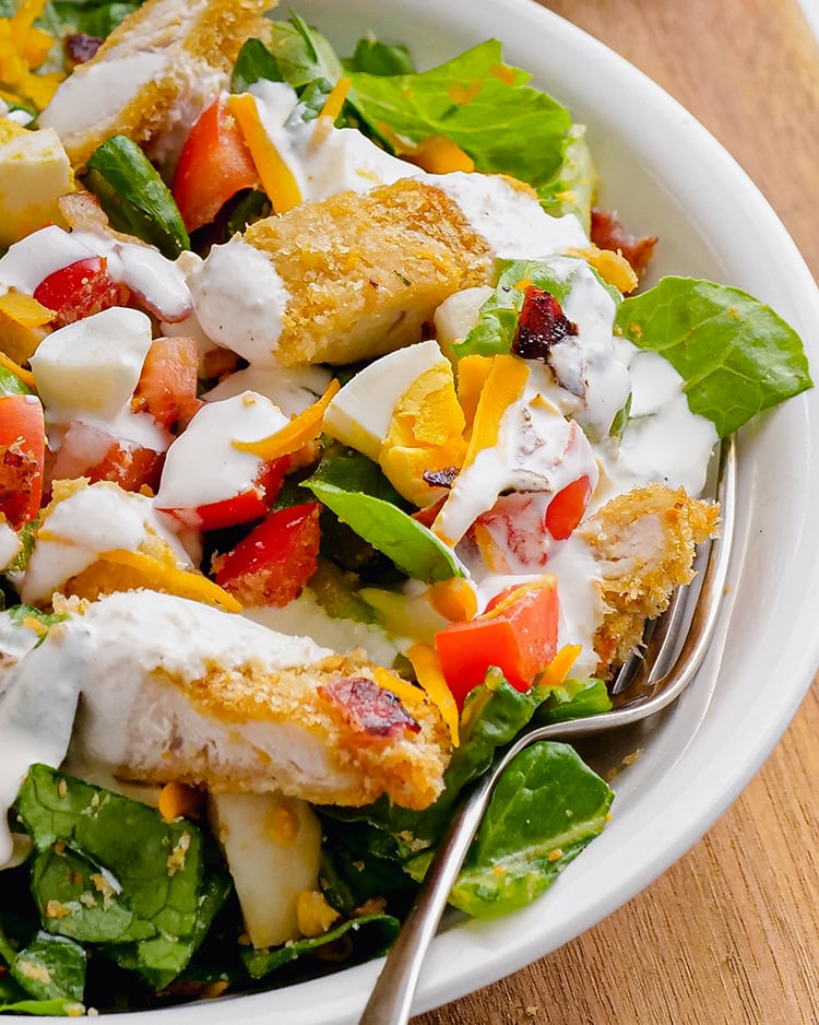 A close up of a chicken salad covered in ranch dressing.
