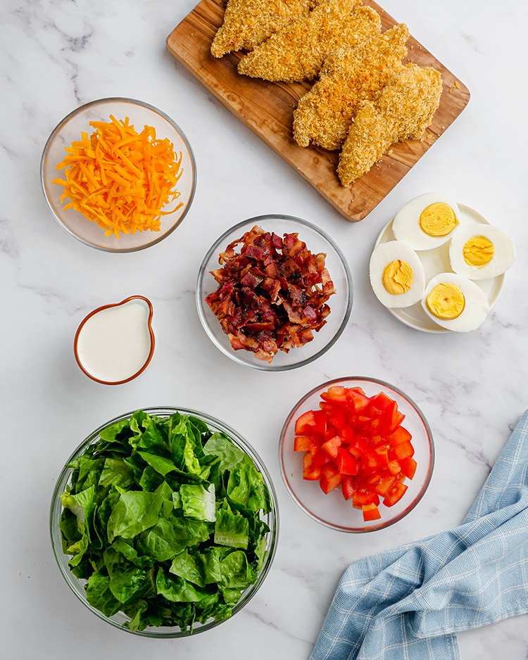 The ingredients in a crispy chicken cobb salad in different bowls before putting it together. A bowl of cheddar cheese, bacon, eggs, tomatoes, lettuce, and ranch dressing, and crispy chicken strips on a cutting board.