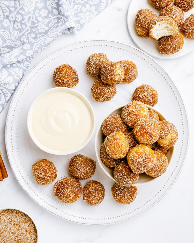 An overhead shot of a plate full of soft pretzel bites, shaped like little golf balls, and covered in cinnamon sugar. With a bowl of cream cheese dip next to them.